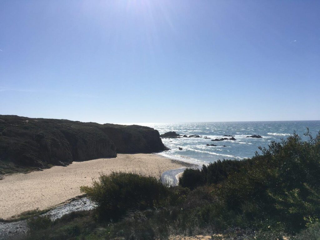 Long stretch of a sandy Almograve beach with a river doen the side and surrounded by cliffs