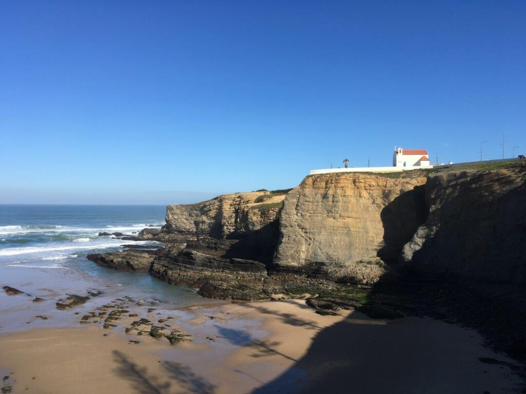 Praia Zambujeira do Mar overlooked by a white church on top of a cliff