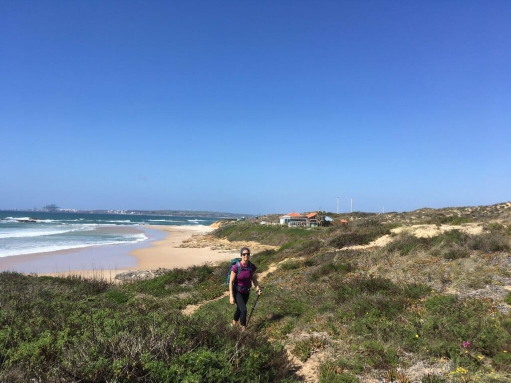 Woman walking by Praia de Vale Figueiros a beach near Porto Covo Portugal