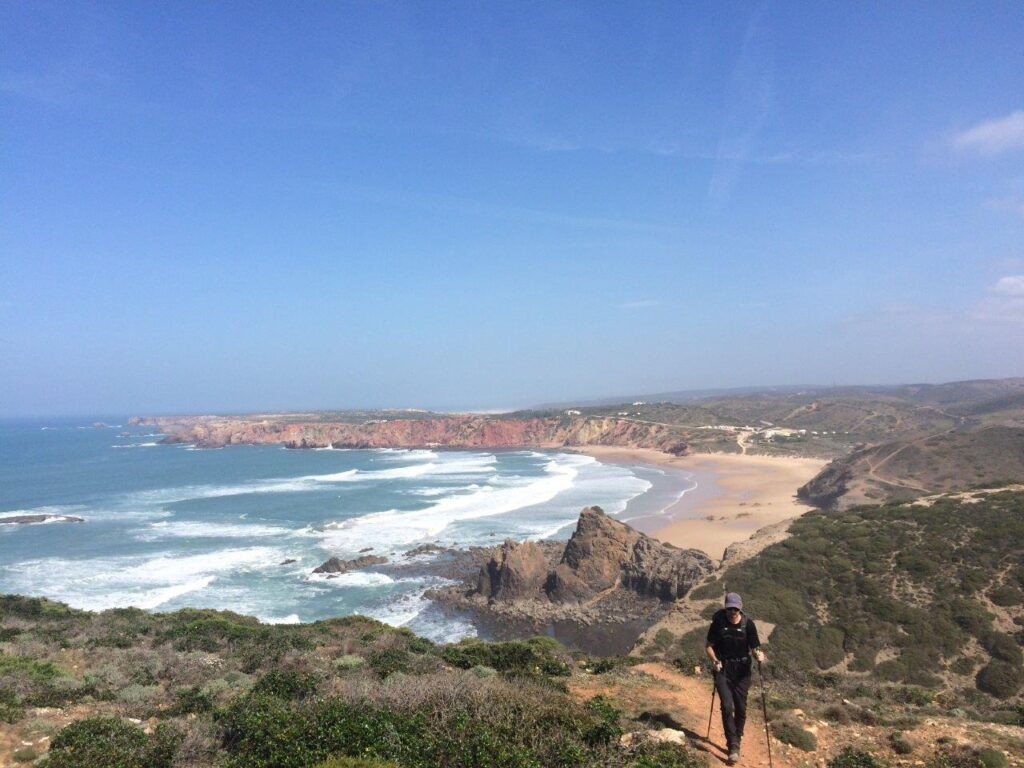 Man hiking on trail above Praia do Amado Portugal