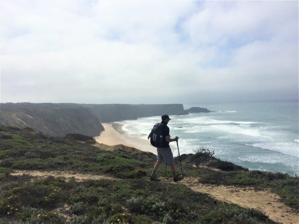 Man walking on hiking trail on top of cliff in front of beach near Aljezur Portugal
