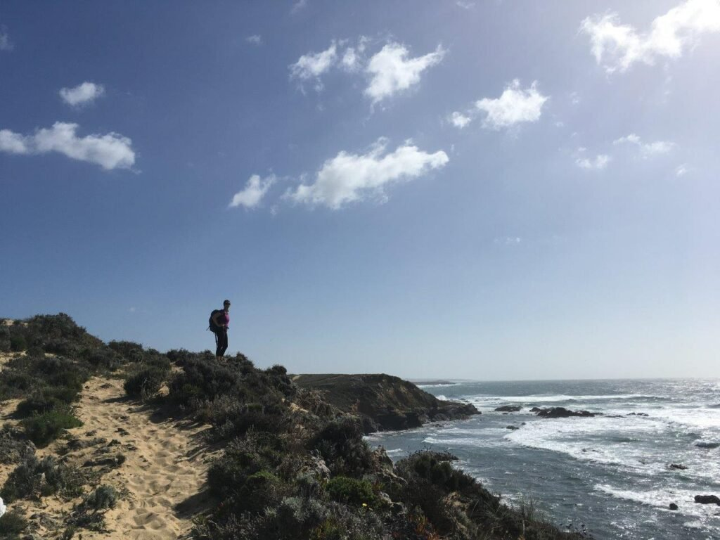 Woman standing on cliff overlooking ocean near Porto Covo Portugal