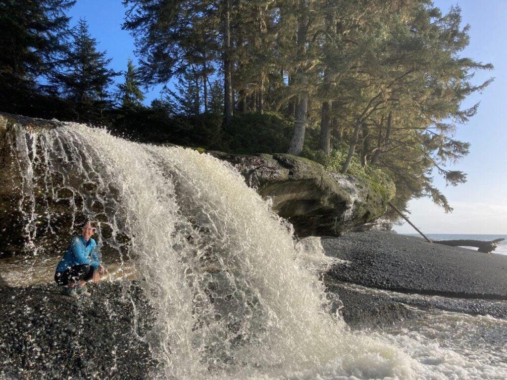 Woman crouching behind waterfall
