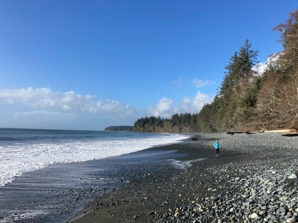 Woman walking on the rocky Sandcut Beach Sooke with forest and large driftwood