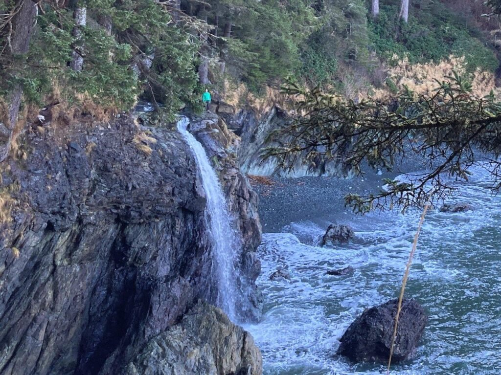 Woman standing at the top of the second Sombrio Beach waterfall that lands in the ocean