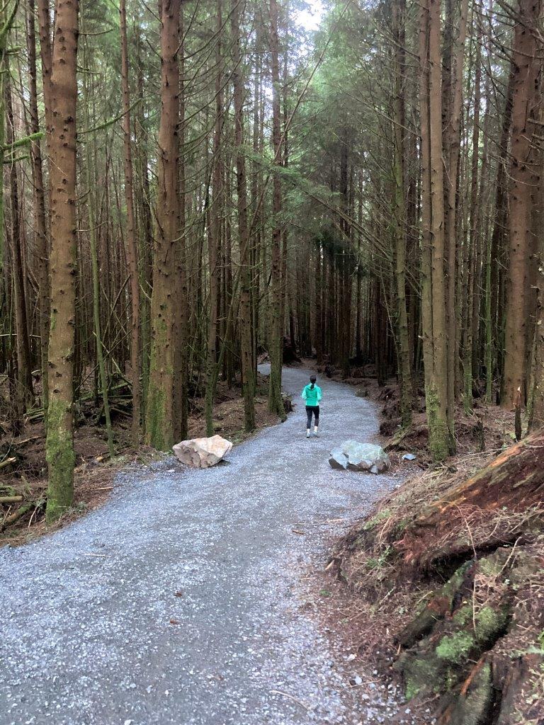 Woman walking on trail with tall tree on each side on way to Sombrio beach one of the things to do in Port Renfrew BC
