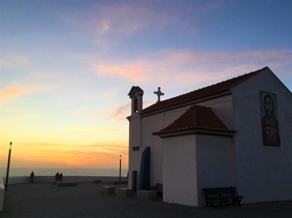 The sun setting behind the church in Zambujeira do Mar Portugal