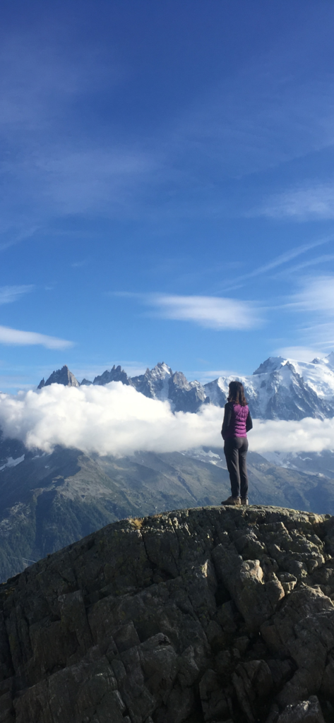 Woman standing on hill looking at Tour du Mont Blanc montains