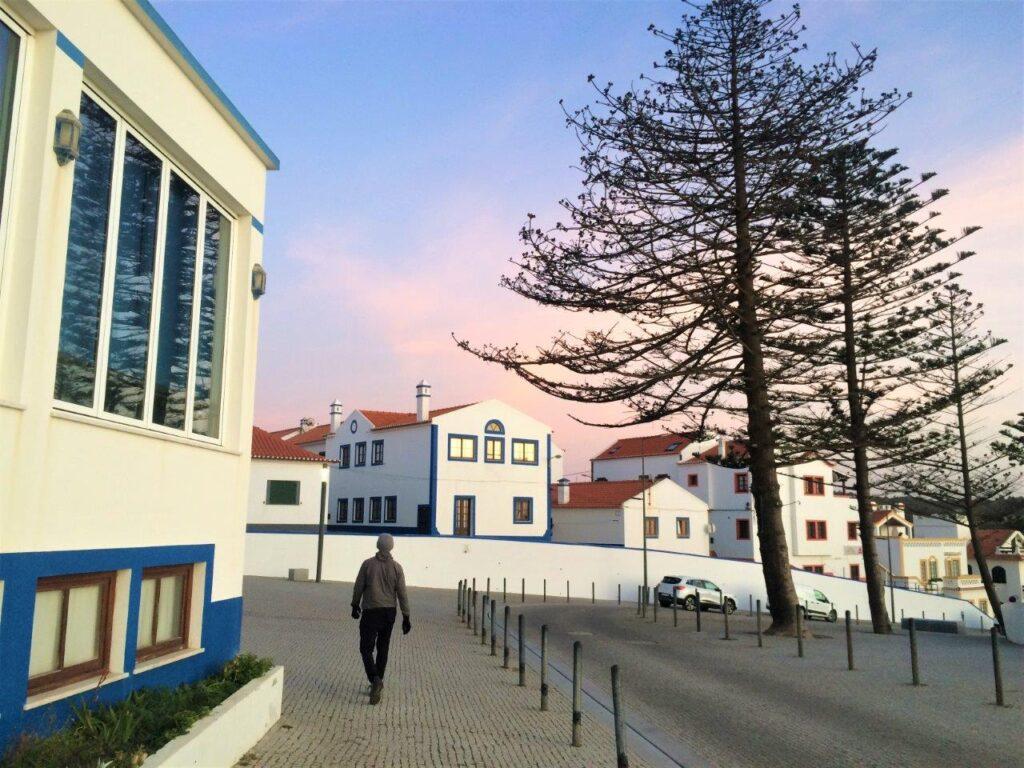 Man walking along the street into a sunset in Zambujeira do Mar Portugal
