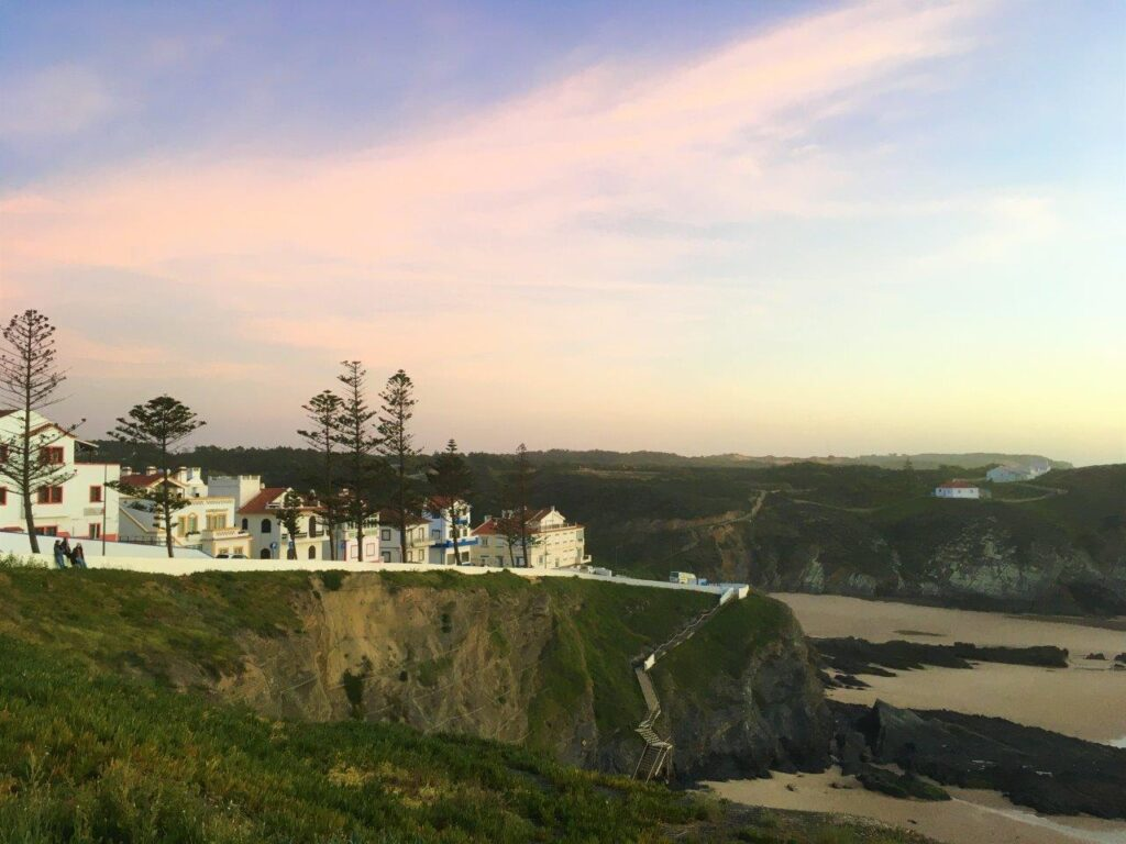A village on a cliff with a beach below and sunset on the Vicentina Coast Portugal