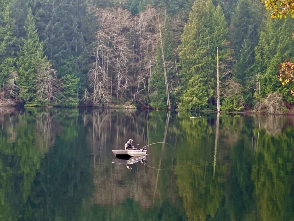 A man in a small boat on Durrance Lake fishing with trees reflected in the water
