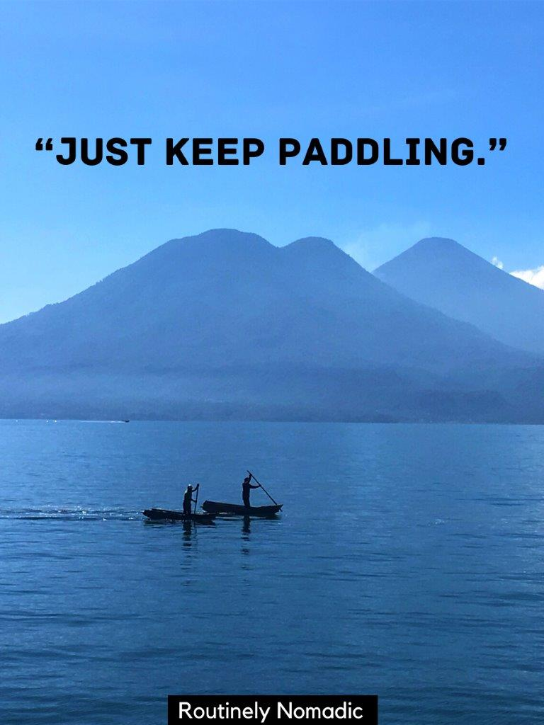 Two men paddling traditional canoes in a lake with volcanoes behind with a funny lake quotes on top