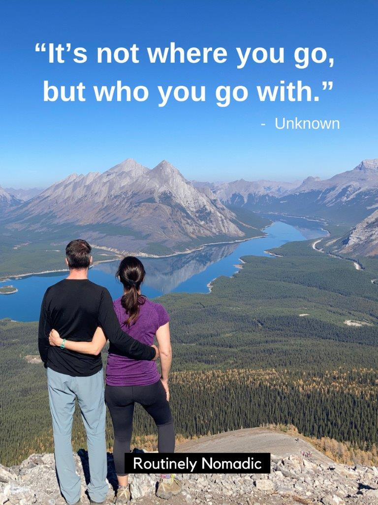 Couple with arms around each other looking at view of lakes and mountains with a hiking quotes for couples on top