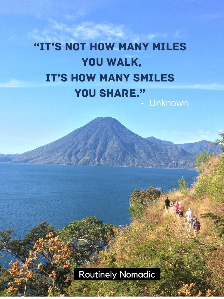 Line of 5 people hiking on trail on hill with lake and volcano in background and a hiking with friends quotes on top