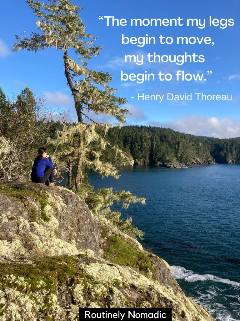 Woman sitting on rock looking at coastline and a inspirational hiking quotes on top