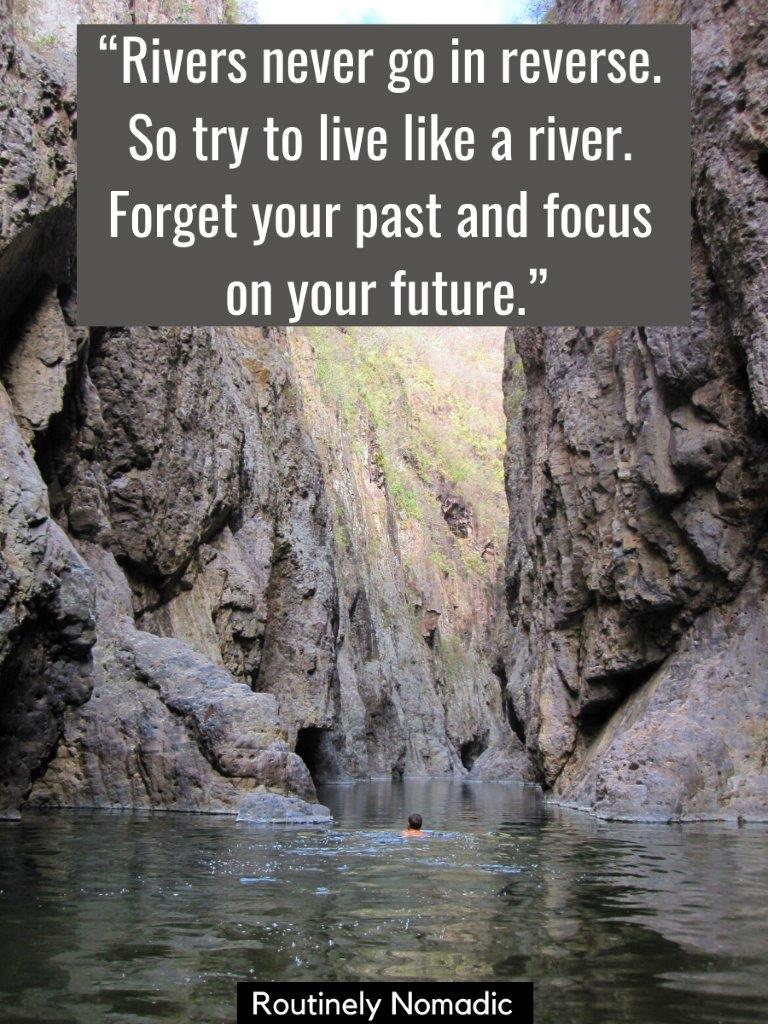man swimming down river with tall canyon walls on both sides with a inspirational river quotes on top