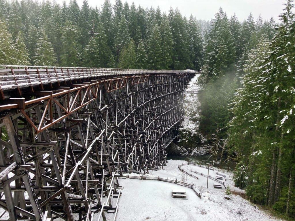 Large Kinsole Trestle bridge made of wood crossing a river with snow and green trees