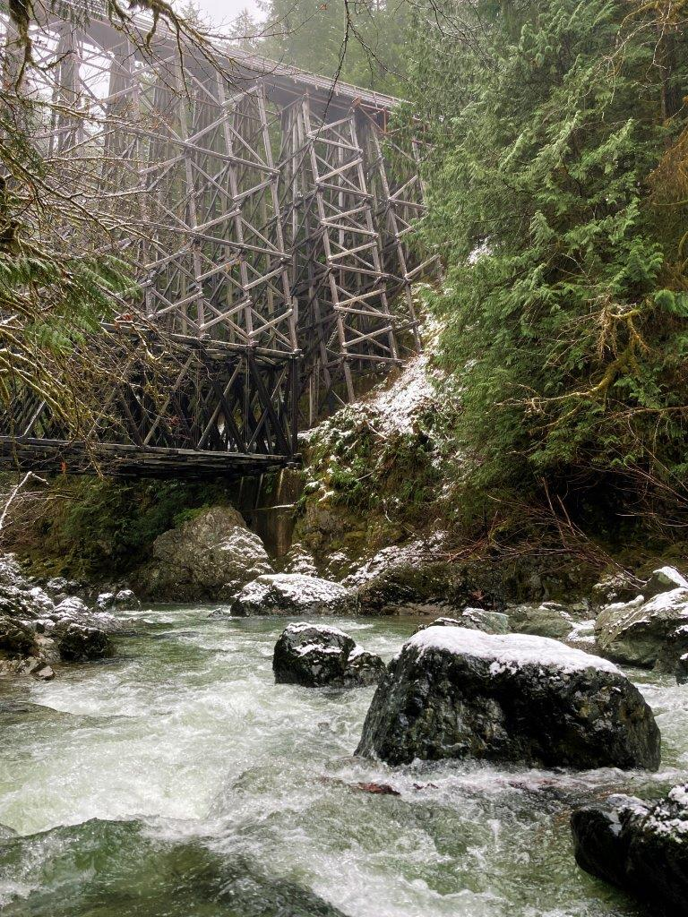 River with snow covered rocks and Kinsol Trestle towering above