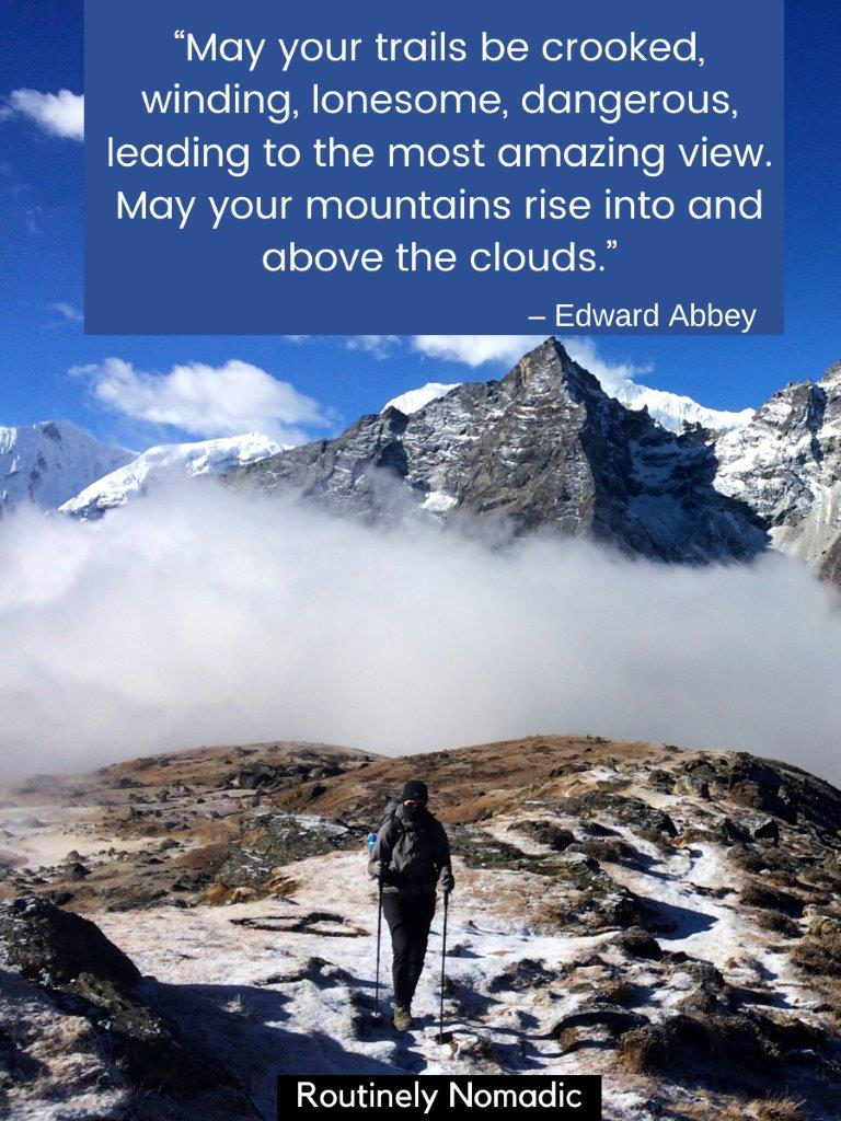 Man hiking away from mountain with low cloud in front and a mountain trekking quotes on top