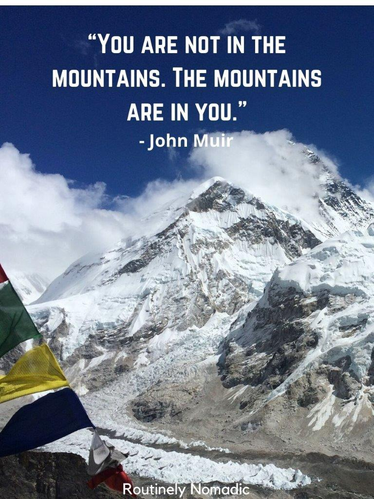 Snow covered mountain with prayer flags in front and a short instgram captions for mountains on top