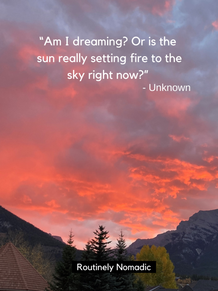 Sunset with mountains and trees in front with a sunset and the sky captions on top