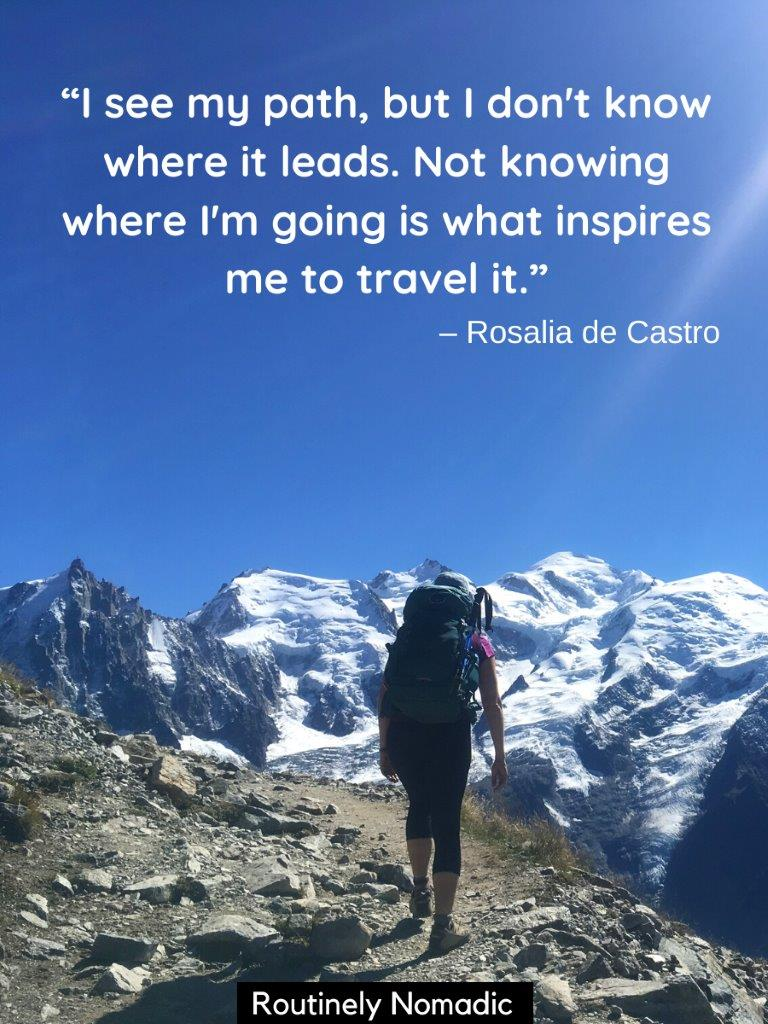 Woman walking on path towards mountain with a quotes about trekking on top
