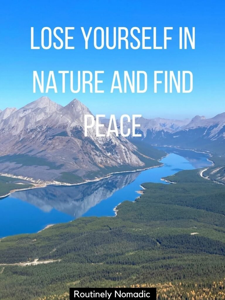 View from above of mountains reflected in a lake with a captions for nature photos on Instagram on top that reads lose yourself in nature and find peace