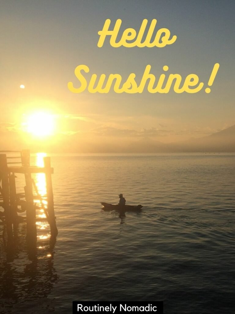 Man on canoe and the rising sun over a lake with a captions on sunshine for instagram on top that says hello sunshine