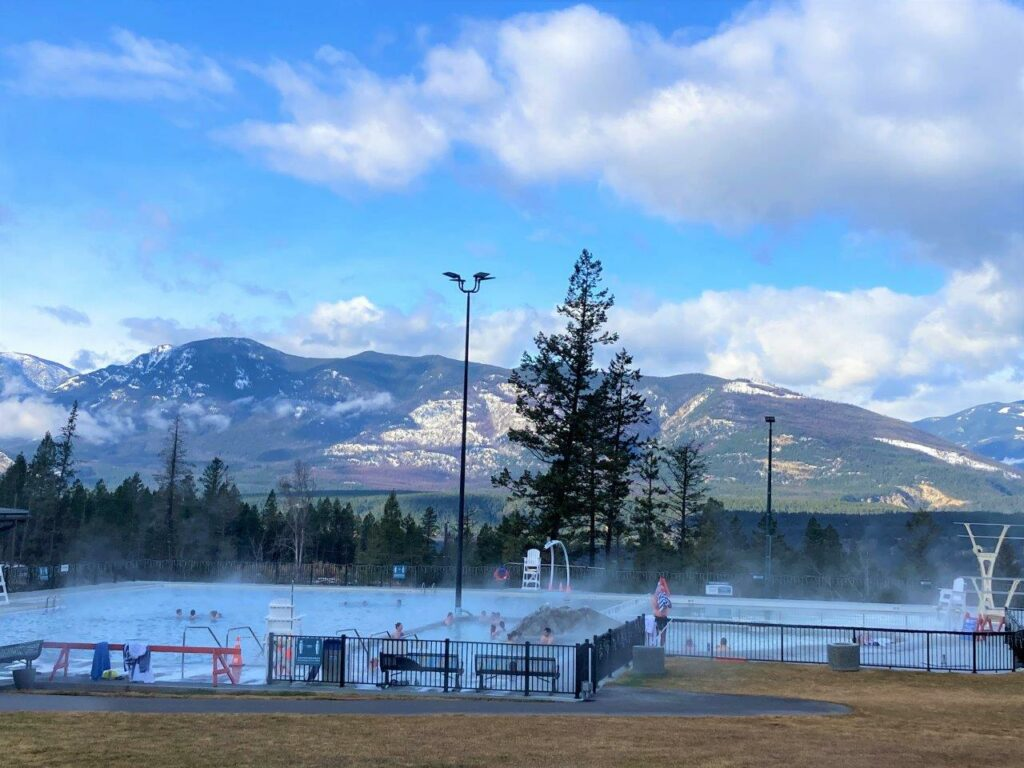 People in the Fairmont hot springs near Invermere with mountains in the background