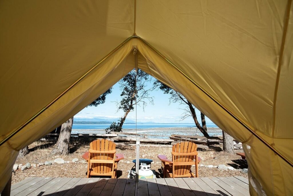 view out the front of a glamping tent with a deck and two chair out front and a ocean with mountains behind at camping Hornby Island