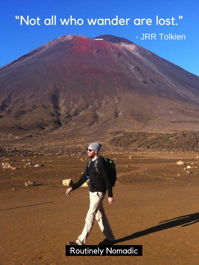 Man walking in front of red conical mountain with hiking quotes for Instagram that reads not all who wander are lost