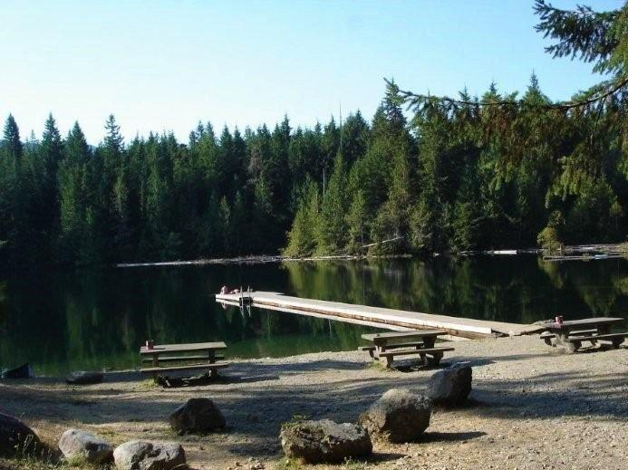 Picnic tables and dock at Lizard Lake one of Port Renfrew camping options