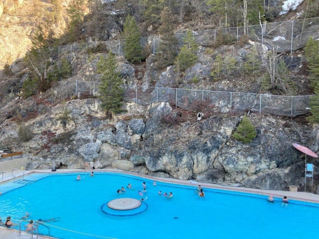 People in the Radium hot springs near Invermere with a rock face behind the pool