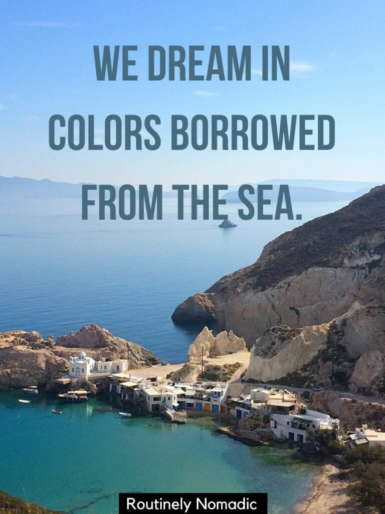 Row of buildings stretching into the sea with a sea captions for Instagram reading we dream in colors borrowed from the sea