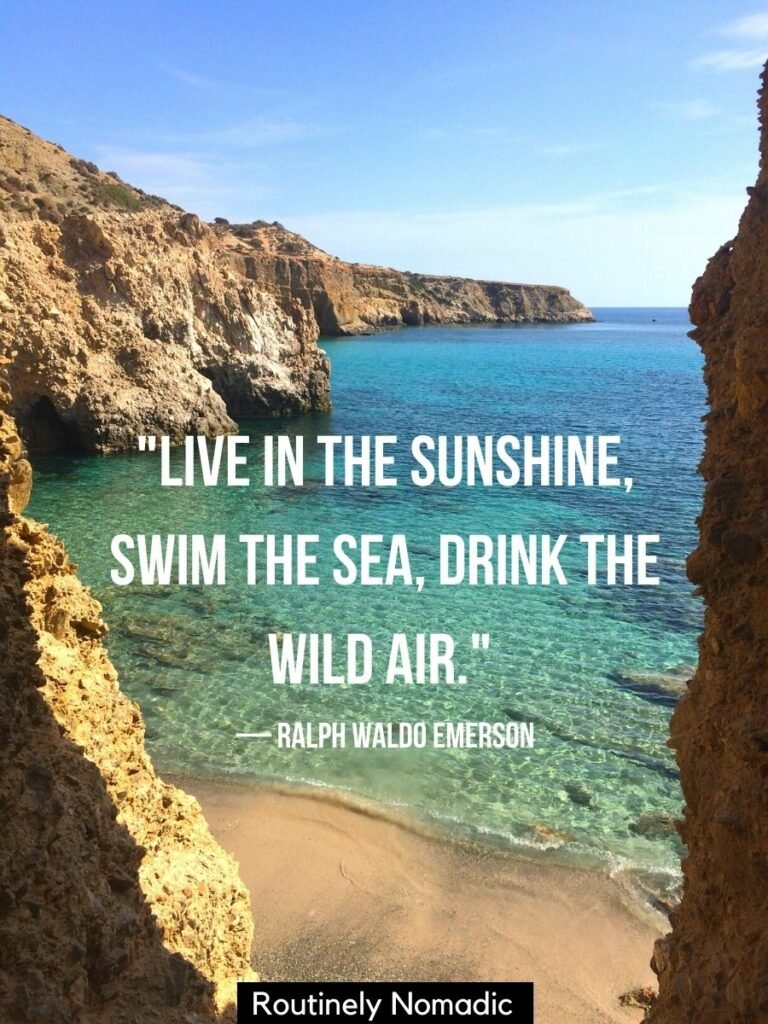 Looking down on a beach with a blue sea from a cliff with a sea quotes for Instagram reading live in the sunshine swim in the sea drink the wild air.