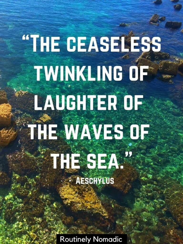 Clear blue and green sea water wtih rocks and sandy bottom with a short sea quotes that reads the ceaseless twinkling of laughter of the waves of the sea
