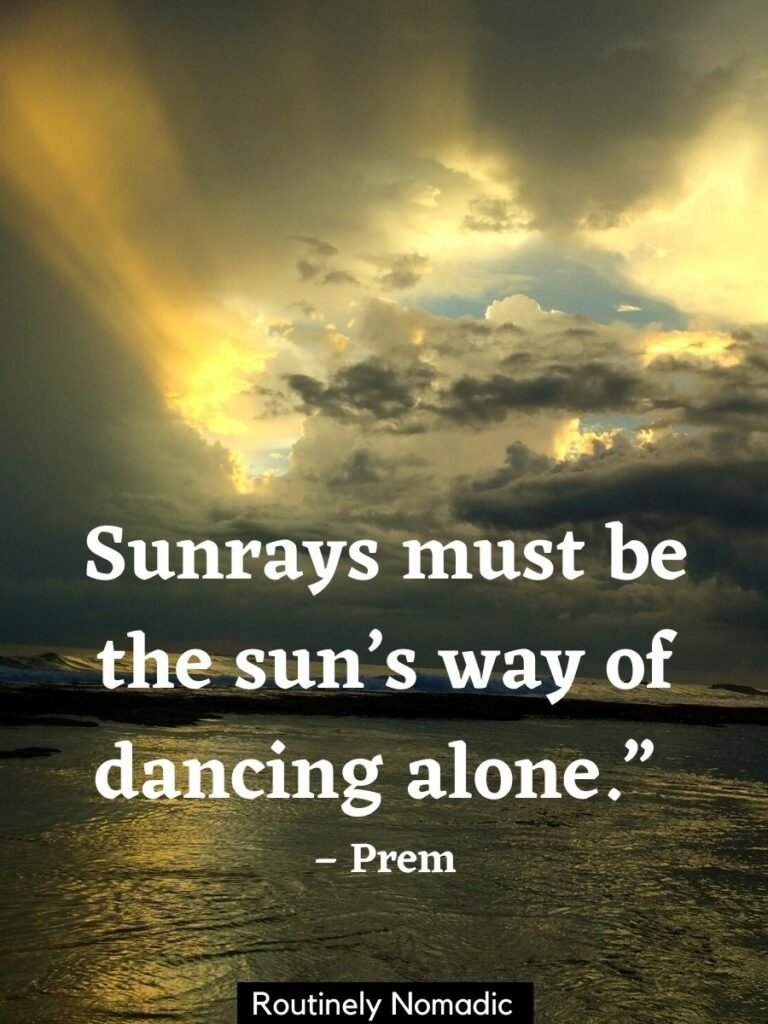 Dark ocean and sky with golden sunrays shining through the clouds an a sunray quotes on top