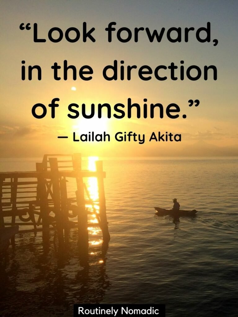 Sun coming over the horizon silhouetting a fisherman in a traditional canoe and a wood dock with a short sunshine quote for Instagram that reads look forward in the direction of the sunshine