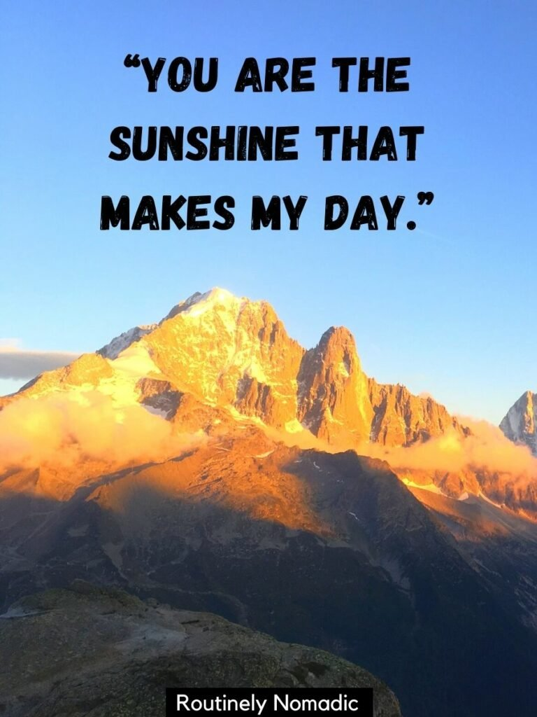 A mountain with snow in the early morning sun with a you are my sunshine quotes that says you are the sunshine that makes my day
