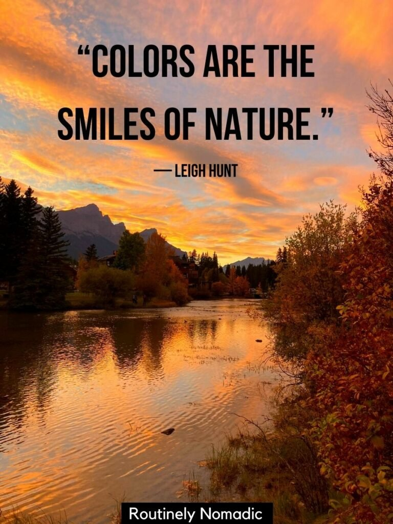 An orange sunset reflected in a lake with mountains behind with a short nature quotes that reads colors are the smiles of nature