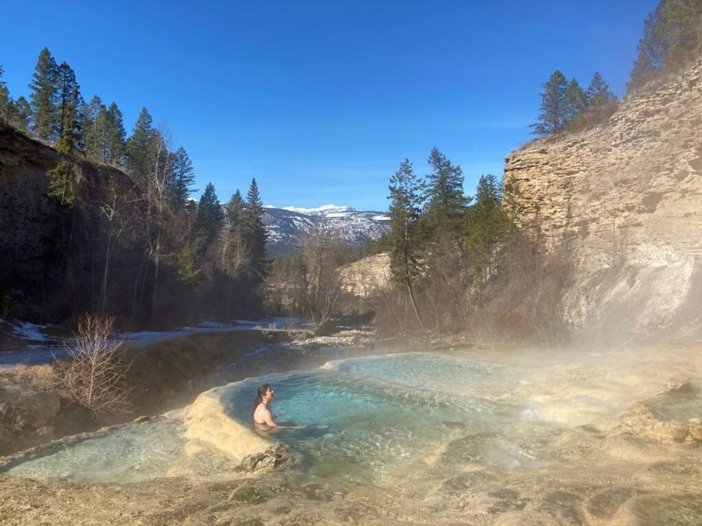Woman sitting in natural hot spring Invemere with no name and a waterfall out of sight