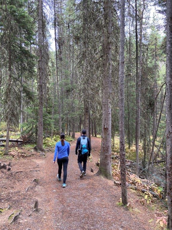 Two people walking on the trail to the lower falls on the Johnston Canyon hike