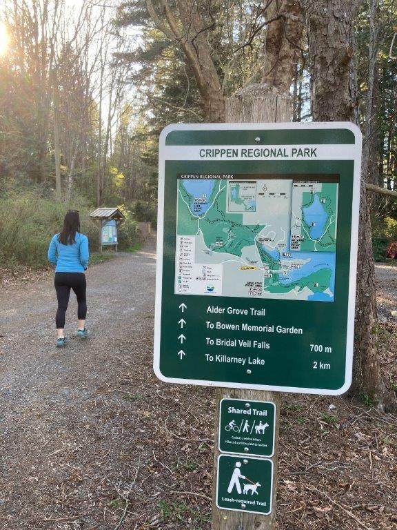 A woman walking past a Bowen Island hike trail map