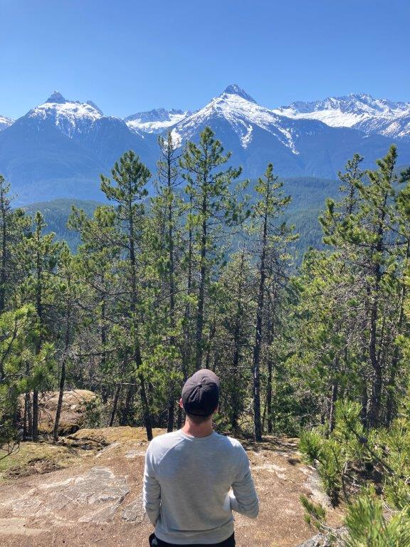 Man looking at snow covered Tantalus Mountain range on one of the best Squamish hikes