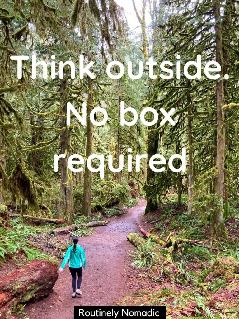 Woman walking on trail with tall trees with a funny hiking captions that reads think outside no box required
