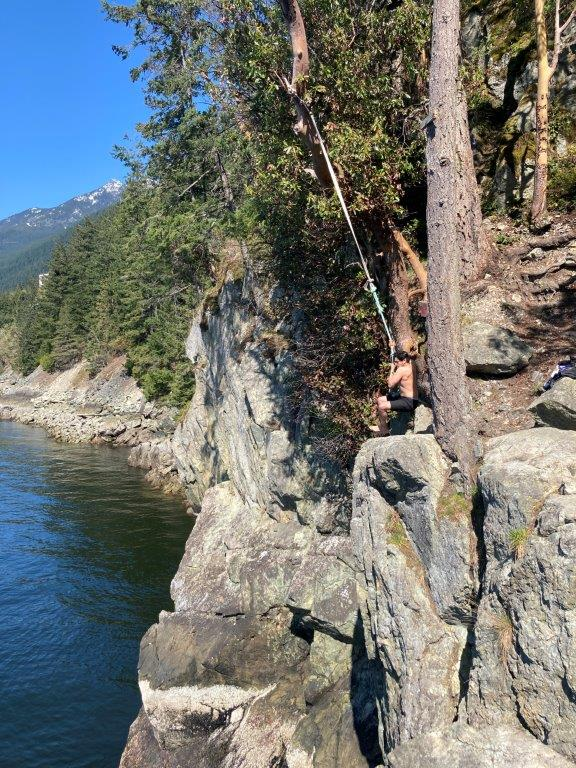 Man starting the rope swing at the Lions Bay cliff jumping spot