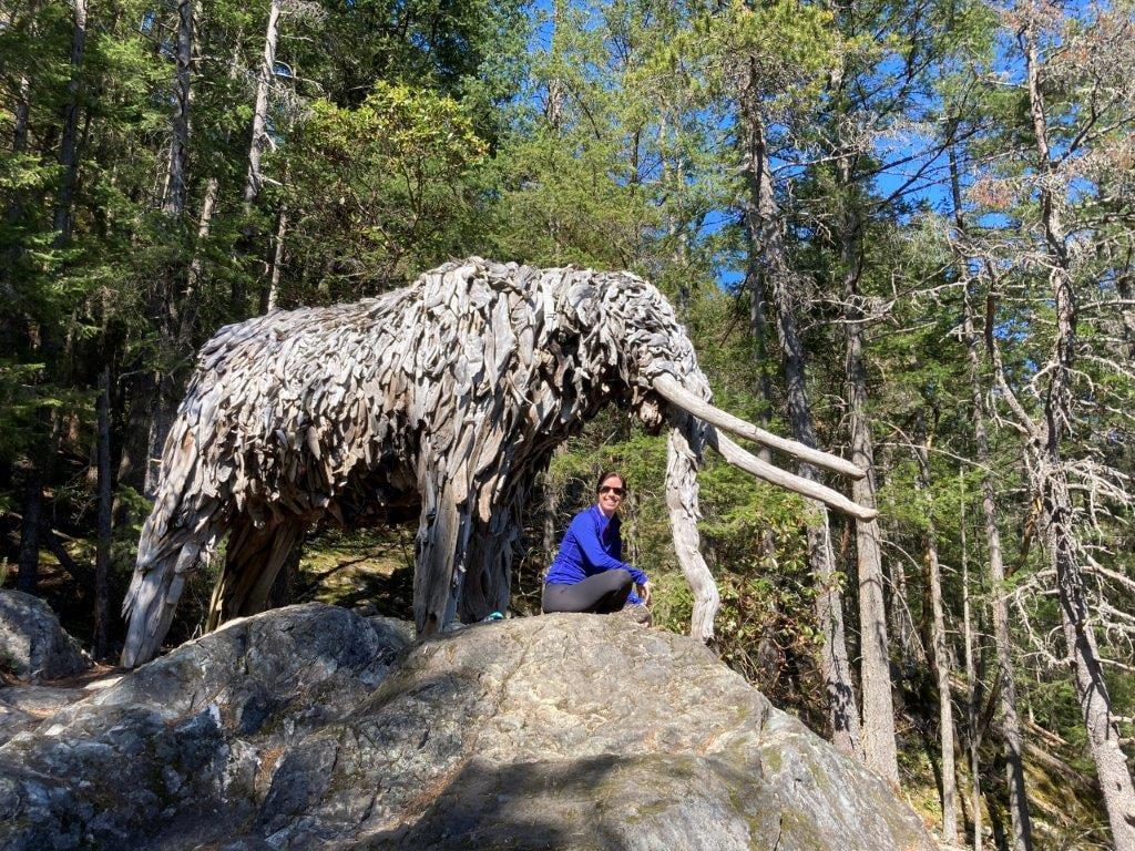 Woman sitting under a driftwood Mastodon sculpture while hiking on Bowen Island