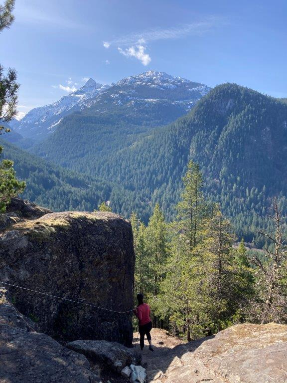 Woman on a rocky Squamish hikes with mountains in the background