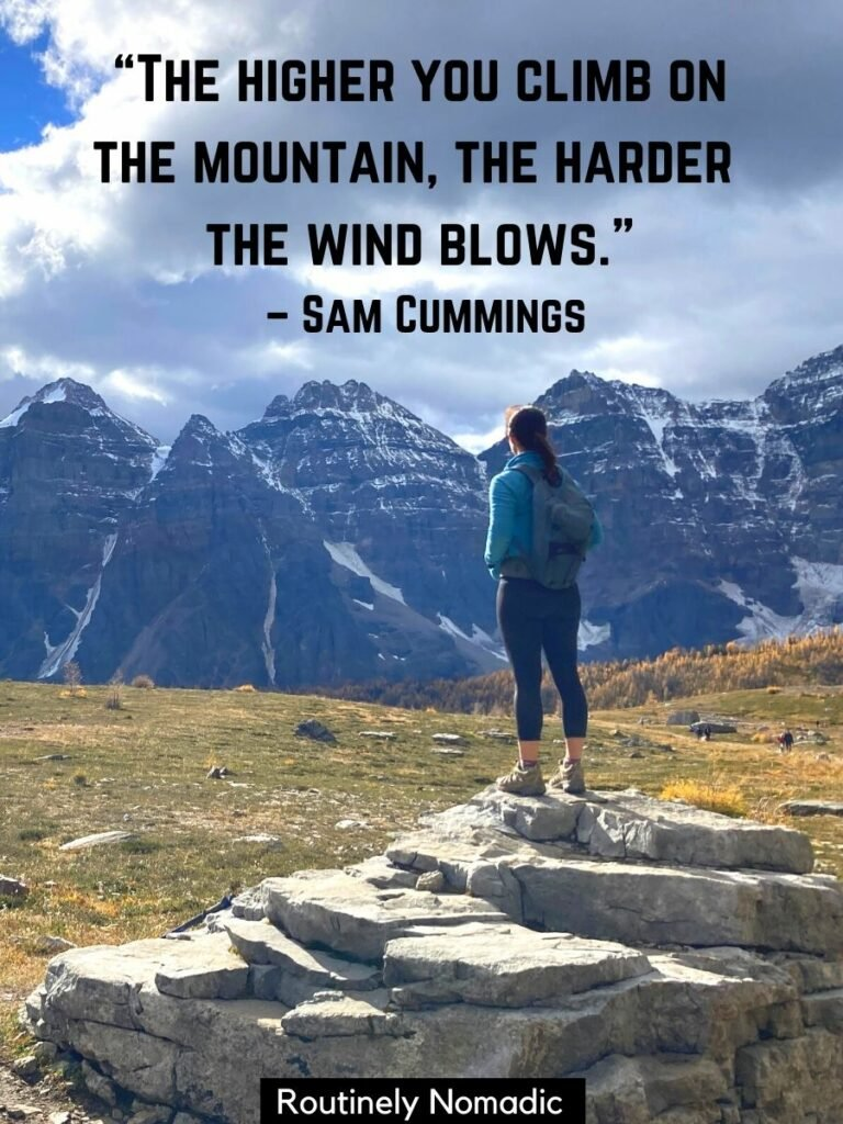 Woman standing on rocks looking at mountains with a mountain quotes funny by Sam Cummings that reads the higher you climb on the mountain the harder the wind blows