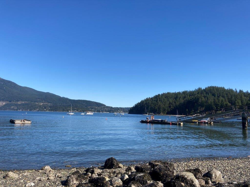View of two docks and a couple sailboats from Pebbly Beach walking distance from Snug Cove on Bowen Island